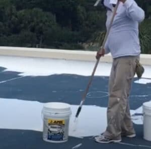 rolling elastomeric roof coating on commercial roof by a Tucson roof coating specialist
